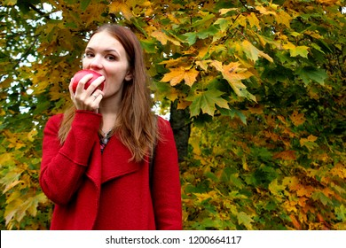 The woman holding fresh apple to eating