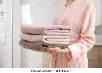 Woman holding fresh towels in bathroom, closeup