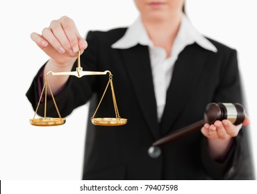 Woman holding a gavel and scales of justice against a white background