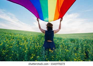 Woman holding the Gay Rainbow Flag on a green meadow outdoors. Happiness, freedom and love concept for same sex couples.