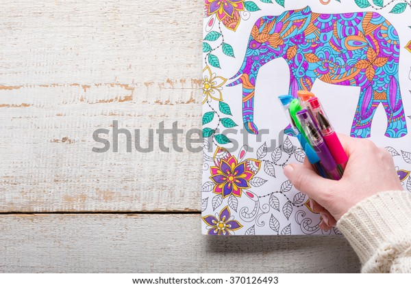 Woman holding gel pens, Adult coloring books, new stress relieving trend, mindfulness concept