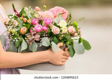 Woman holding gift box with beautiful flowers outdoors