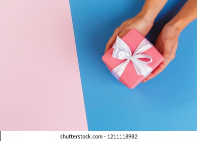 Woman holding gift box on color background