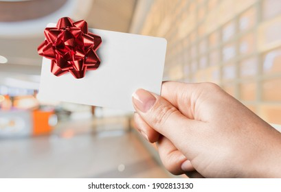 Woman holding gift card in a restaurant or shop