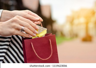 A woman is holding a gift package bag in hand shopping jewerly box ring on blur nature sun background