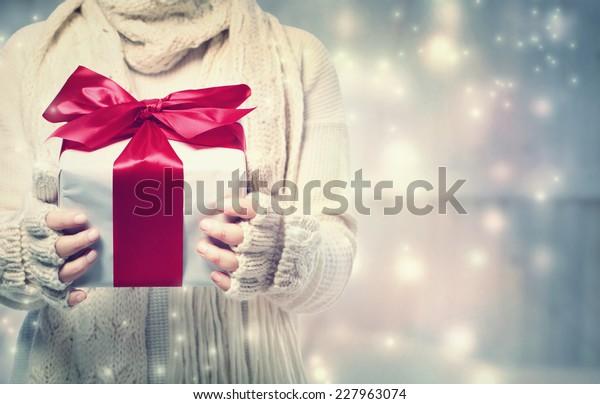 Woman holding a giftbox with red ribbon in the snowy night