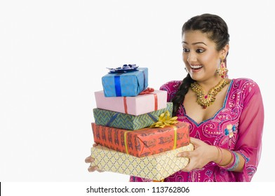 Woman holding gifts and smiling