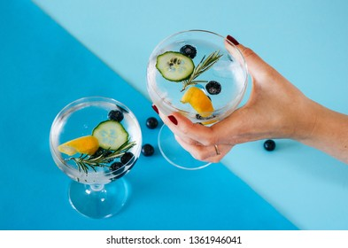 Woman holding a gin and tonic drink with blueberries, cucumber and rosemary on a blue geometric, colorful background.