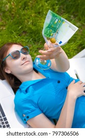 Woman holding glass with 100 euro outdoors