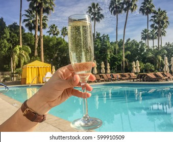 Woman holding glass of champagne in front of pool