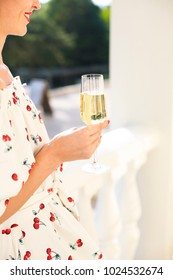 Woman holding glass of champagne. Party with sparkling champagne glasses outdoors. Close up
