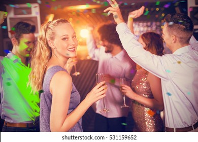 Woman holding glass of champagne while dancing with friends against flying colours