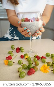 woman holding glass with chiapudding and fresh berries in her hands. Healthy food concept