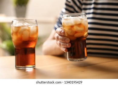 Woman holding glass of cola with ice at table, closeup
