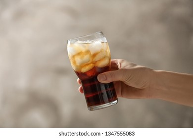 Woman holding glass of cola with ice on color background, closeup. Space for text