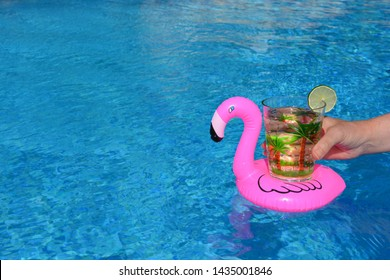 Woman holding glass decorated with tropical palm trees, of sparkling water with a slice of lime, in a pink inflatable drinks holder in a swimming pool.