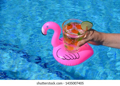 Woman holding glass decorated with tropical palm trees, of sparkling water with a slice of lime, in a pink inflatable flamingo drinks holder in a swimming pool.