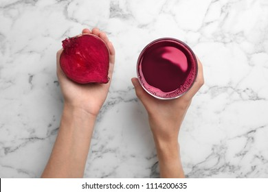 Woman holding glass with fresh beet juice and half of vegetable on marble table, top view