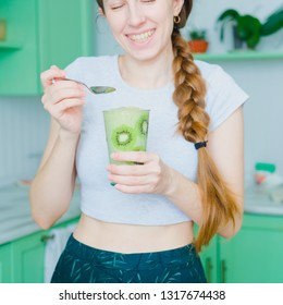 Woman holding glass of Green smoothie of celery and banana in glass decorated with slices of kiwi. Healthy vegan lifestyle.