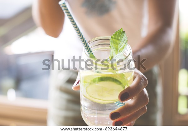 Woman holding glass of infused water with cucumber, lime and mint