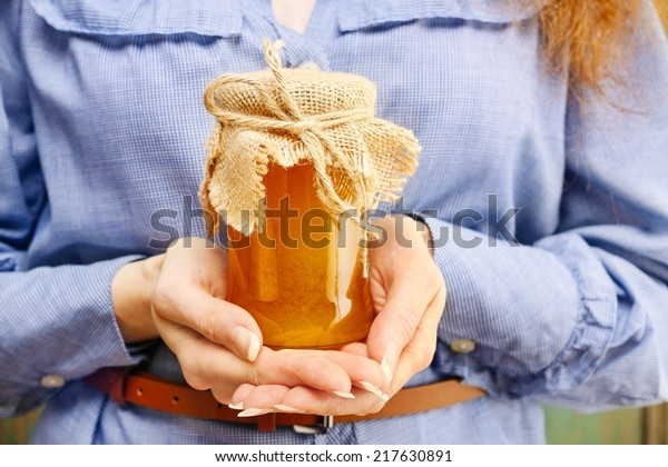 Woman holding glass jar of honey