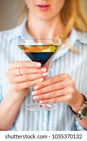 Woman holding glass with martini and green olives, focus on the glass
