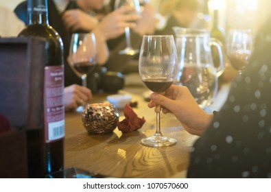 Woman holding glass of red wine. Party in the bar.