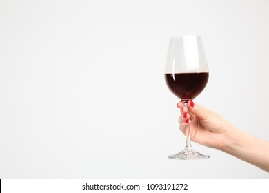 Woman holding glass of red wine on white background