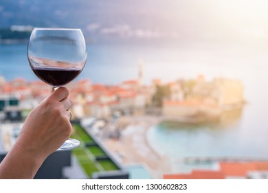 Woman holding glass with red wine on the balcony of her apartment in the Budva town, Montenegro
