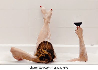 Woman holding glass with red wine and lying in bathroom full of foam. Relaxing at home