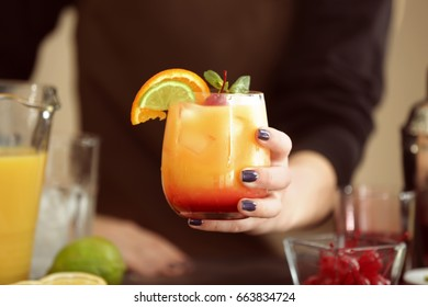 Woman holding glass of Tequila Sunrise cocktail