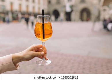 Woman holding a glass of traditional Italian aperitif on the background of the old town. Lifestyle concept, space for text. Aperol spritz cocktail.