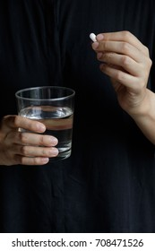 Woman holding a glass of water and pill. Take a pill. Medication
