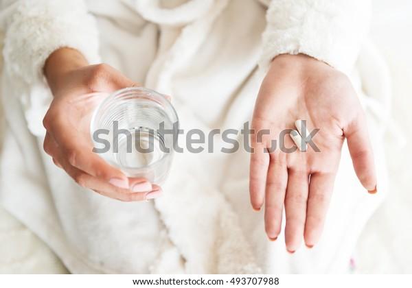女人拿著一杯水和藥丸,細節