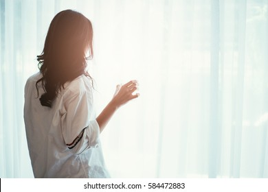 Woman holding a glass of water while looking out of the window - back of silhouette woman