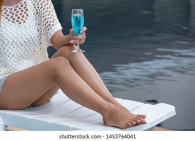 Woman holding glass of wine by swimming pool, travelling and relaxing time concept, close up.