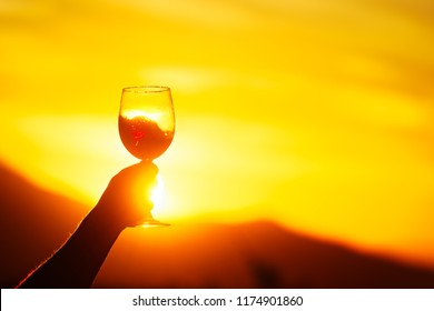 Woman holding glass of wine on the background of beautiful sunset in Georgia(country)