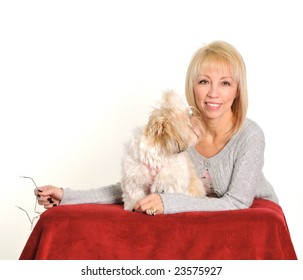 Woman holding glasses and a dog looking at her.