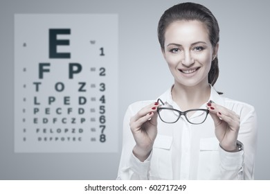 Woman holding glasses in hands with Snellen test chart on background.
