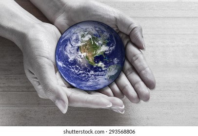 Woman holding global in hands , Elements of this image furnished by NASA