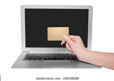 Woman holding gold credit card in hand. On-line shopping on the internet using a laptop.