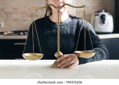 Woman is holding golden balances on the kitchen