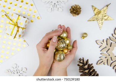 Woman holding golden christmas balls. Girl preparing for holidays, decorating for Christmas tree. Flat lay, top view. White table with female hands holding various trinkets, decor accessoires