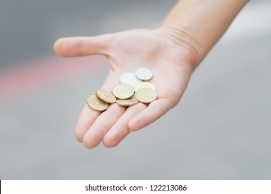 Woman holding golden and silvery coins (shekels) in her hand