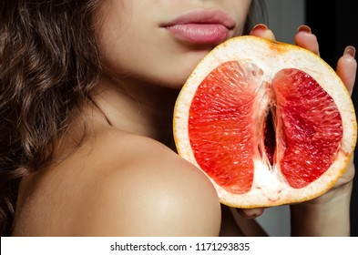 A woman is holding a grapefruit by her lips. Concept masturbation