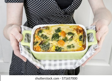 Woman holding a gratin in green bowl.