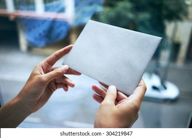 woman holding gray envelope on the city background