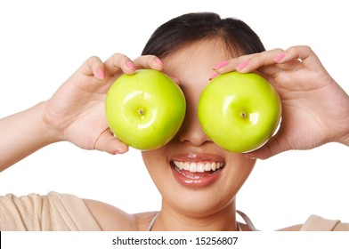 Woman holding green apple in front of her eyes
