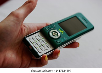 Woman is holding a green Sony Ericsson W580i Walkman released August 2007, Wales, United Kingdom. Mobile phone with buttons from Virgin Mobile contract.