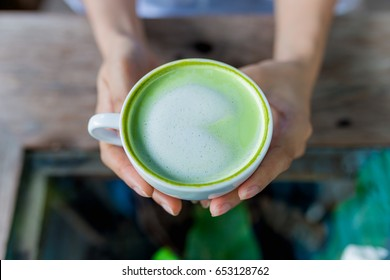 Woman holding  green tea latte on wooden table.